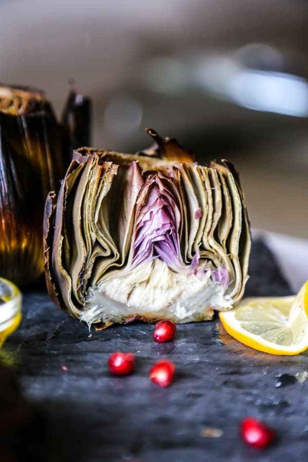 a roasted artichoke with lemon sliced in half