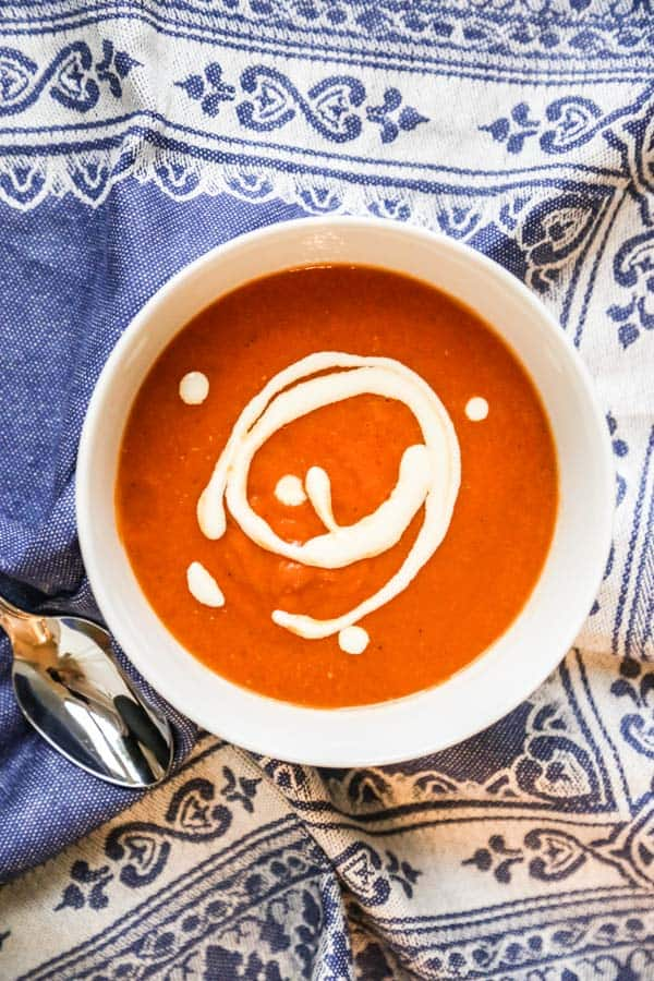 dairy free tomato soup in a bowl with white cream garnish on a blue tablecloth