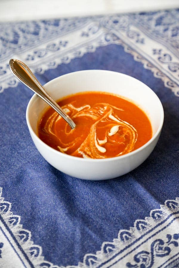 dairy free Vegan tomato soup in a white bowl with a spoon on a blue tablecloth