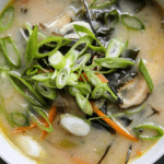 a bowl of miso soup with shiitake mushrooms celery carrots ginger garlic and miso