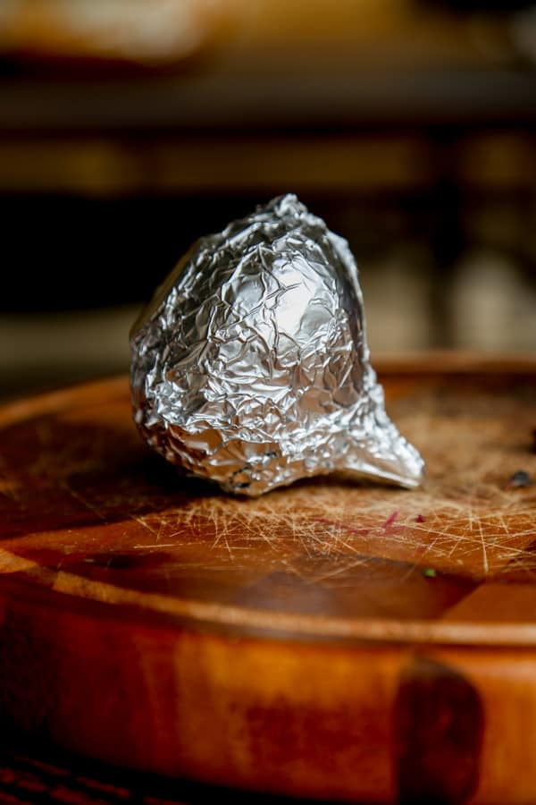 a beet wrapped in tinfoil on a cutting board.