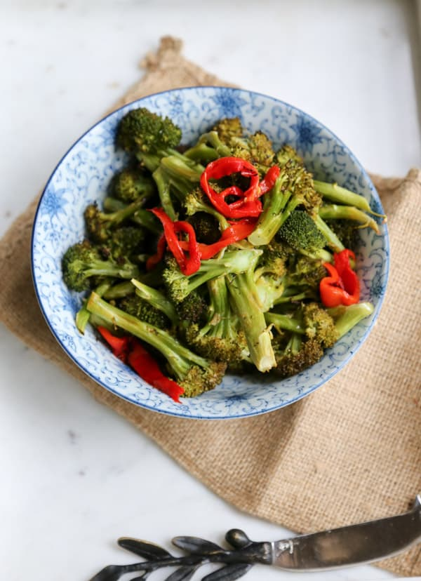 Roasted Broccoli with Lemon and Butter in a blue and white plate with peppers
