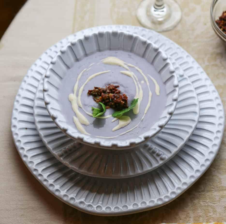 simple cauliflower soup on a plate garnished with mint and tapenade
