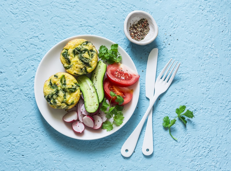 mini frittatas with lacinato kale and shallots on a white plate with a salad on a blue table with knife and fork