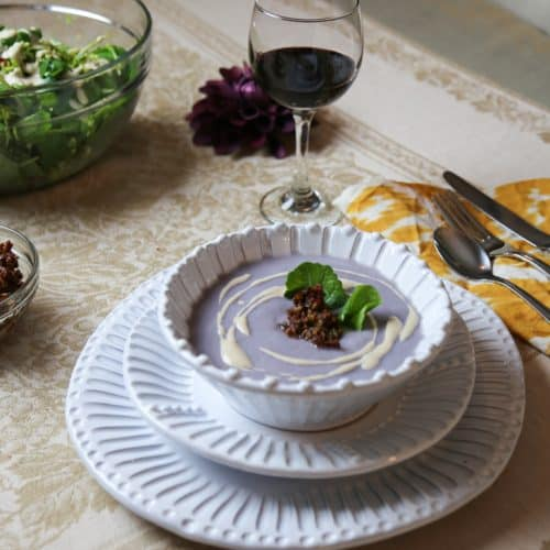 Simple Cauliflower Soup with Sundried Tomato Tapenade in a bowl on two white plates with a glass of wine