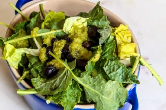 a bowl of green salad with black beans and guatemalan dressing on a white table