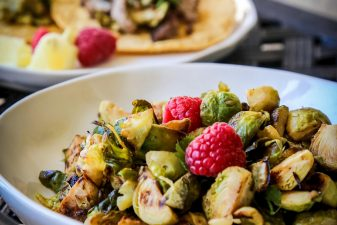sautéed brussels sprouts in a white bowl with raspberries on top