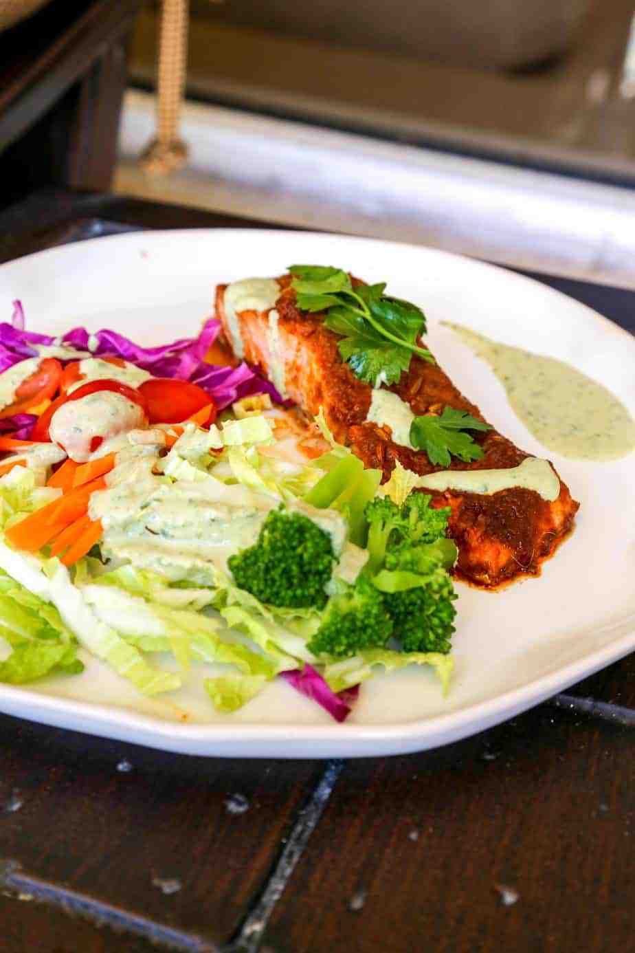 oven baked salmon with Peruvian Spices on a plate with a rainbow salad