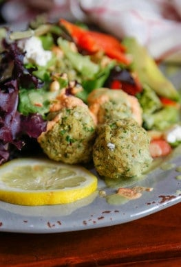 three gluten-free falafel balls on a grey plate with lemon and salad