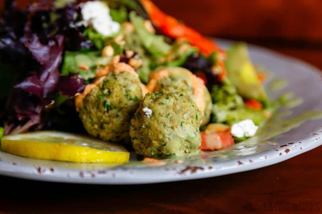 raw vegan falafel recipe. falafel balls on a plate with lemon and a salad
