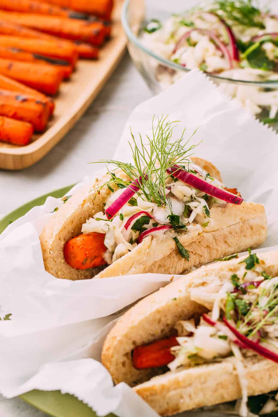 vegan carrot dogs in a hot dog bun topped with sprouts and white sauce