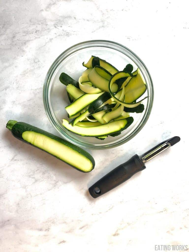 a bowl of zucchini peeled with a vegetable peeler and whole zucchini