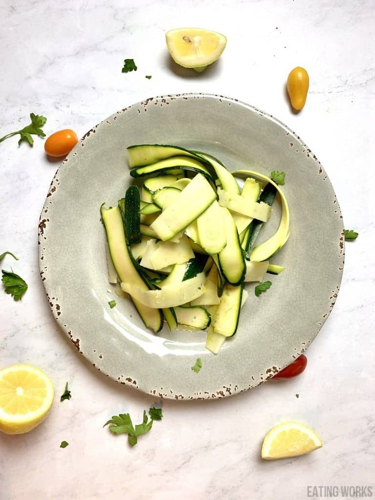 Zucchini Carpaccio with Manchengo Cheese Lemon and Olive Oil on a gray plate
