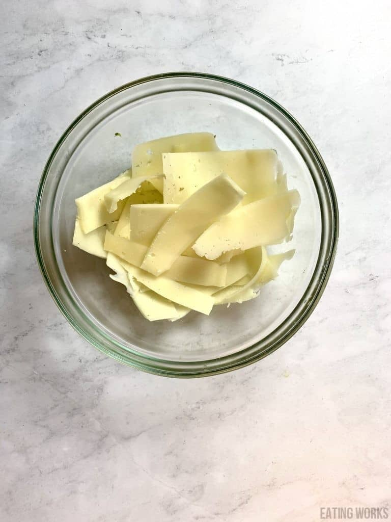 a bowl of shaved manchengo cheese on a marble surface