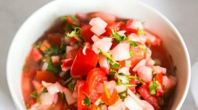 Bowl of shrimp ceviche with tomatoes with a white and red napkin and spoon