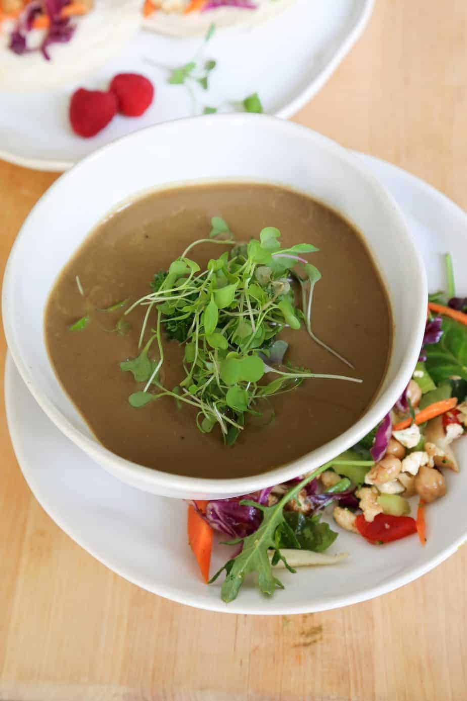 vertical vegan mushroom soup in a white bowl with micro greens