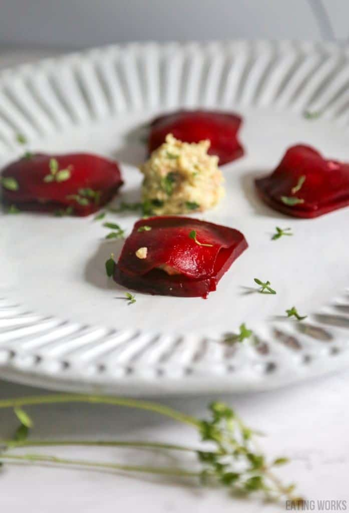 plate of beet ravioli with vegan ricotta on a white plate with thyme garnish