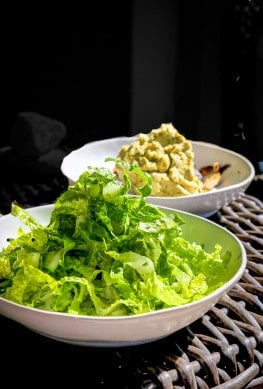 marouli salad in a white bowl on a table with ingredients scallions, romaine lettuce, feta and dill in a lemon vinaigrette with sherry vinegar