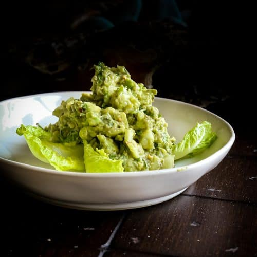 bowl of healthy guacamole with lemon and cilantro with lettuce leaves