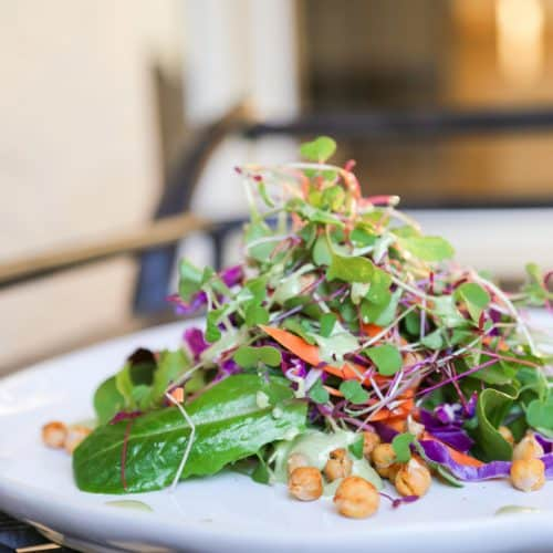 micro green salad with chickpea croutons and green goddess dressing on a plate