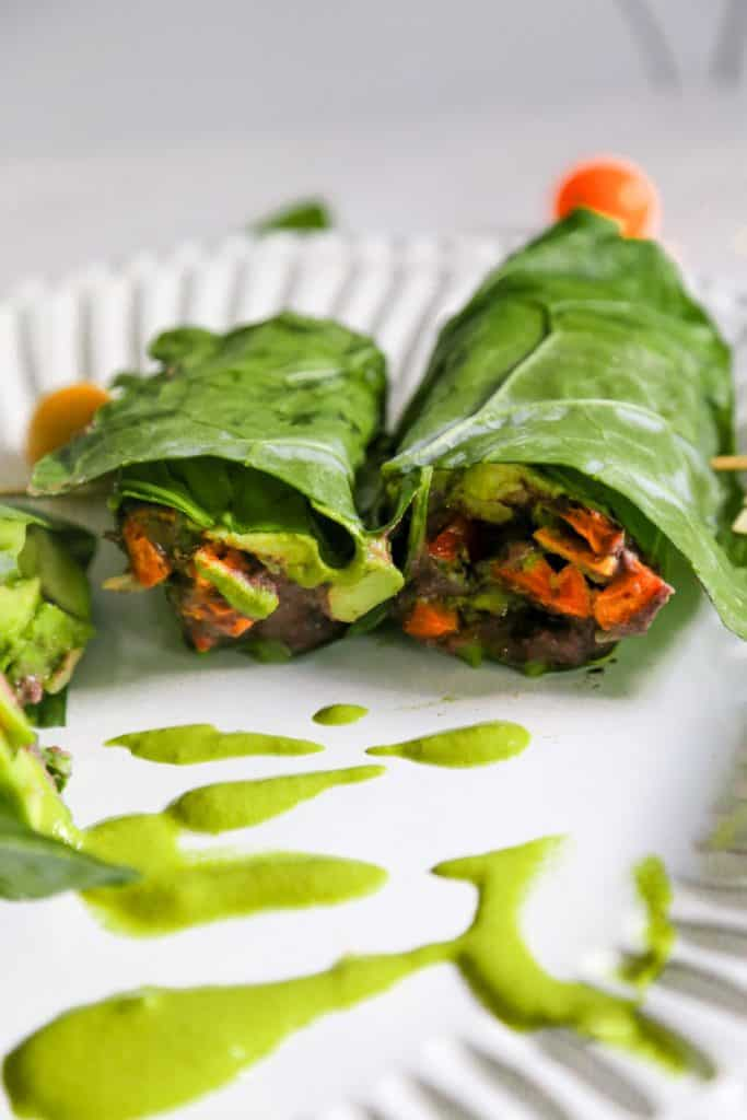 collard green wrap with vegan refried black beans spicy green tahini sauce and cartelized onions and roasted sweet potatoes