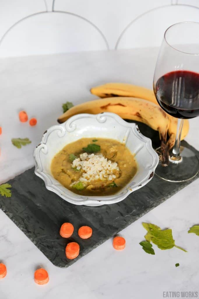 vegan split pea soup from the side in a bowl with wine, bananas, carrots and celery