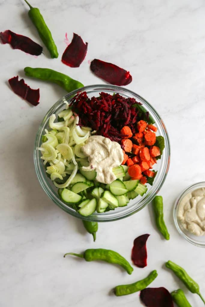 Kale salad with apple tahini dressing in a bowl from above with beets, cucumbers carrots fennel and a dollop of tahini apple dressing