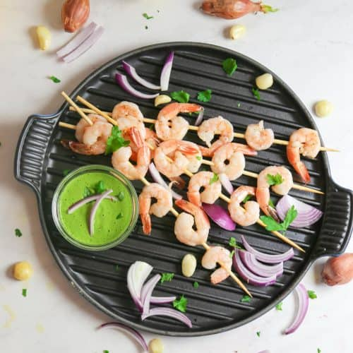 oven baked shrimp kabobs with spicy green tahini sauce on a grill pan from above
