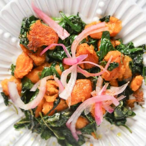 vegan sweet potato gnocchi with sautéed spinach on a white plate made with sweet potatoes and cassava flour