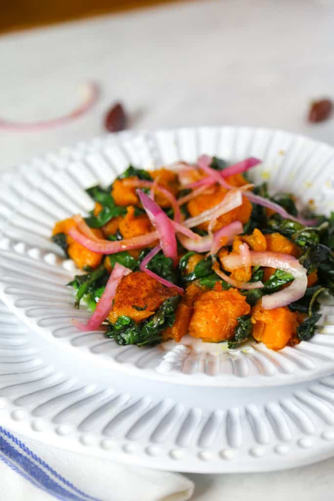 vegan grain free sweet potato gnocchi on a white plate with sautéed spinach with a blue napkin