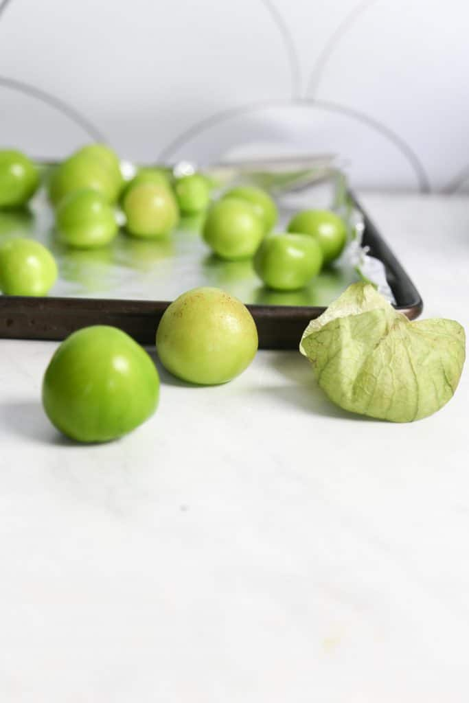 ingredients raw tomatillos on a white counter for spicy tomatillo salsa