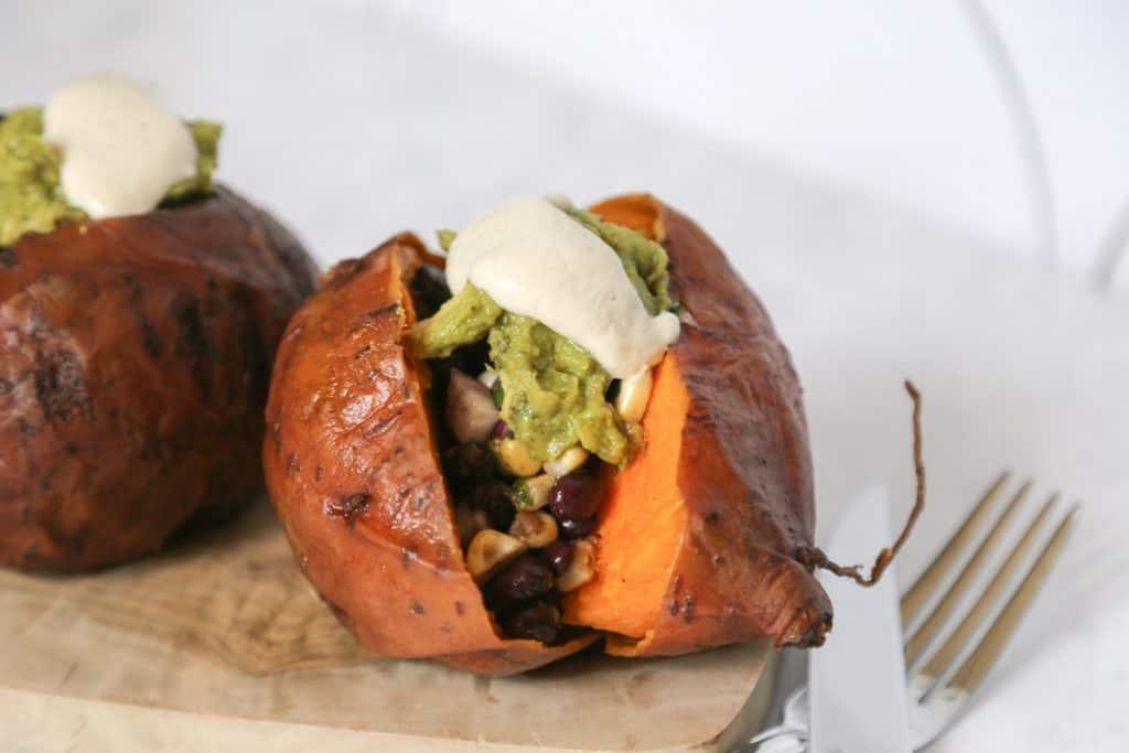 Vegan Stuffed Sweet Potatoes on a plate with a knife and fork. #sweetpotato #vegan #vegansweetpotatorecipe #veganrecipe