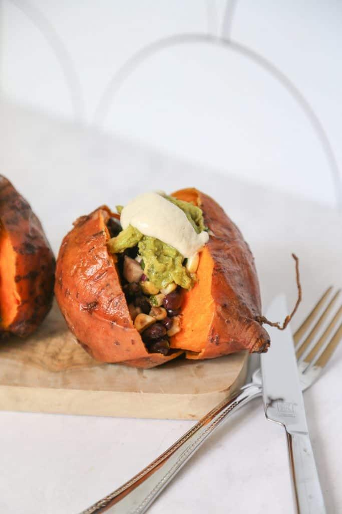Vegan Stuffed Sweet Potato on a cutting board with guacamole, salsa and cashew cream