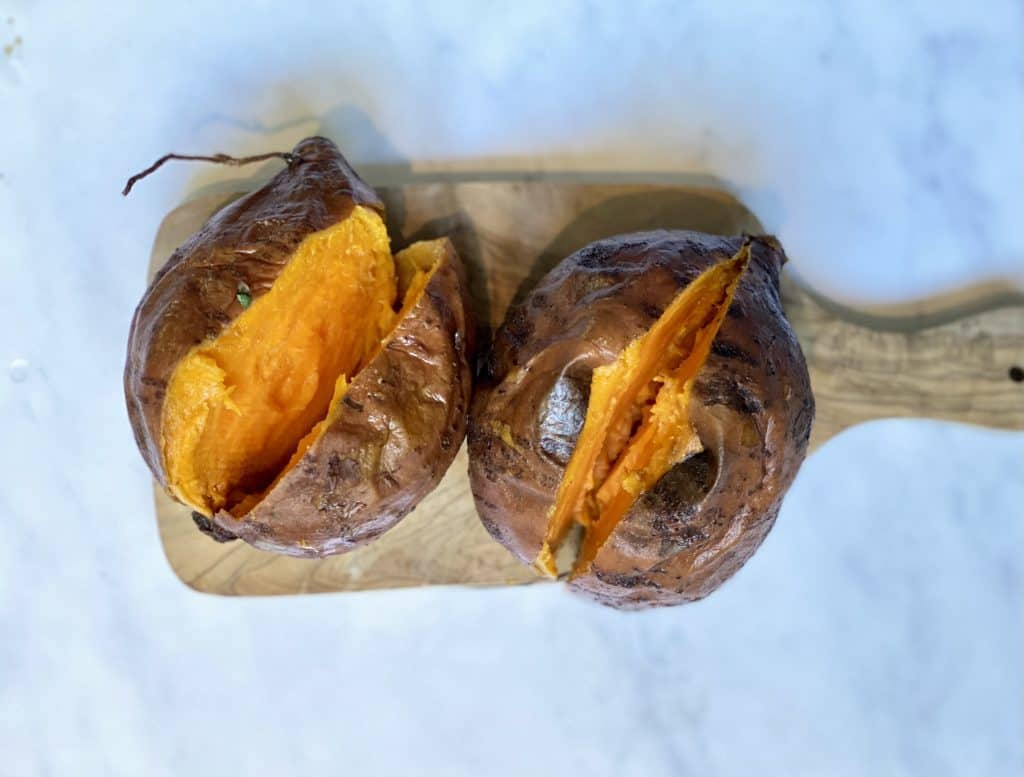 cooked sweet potatoes cut open on a cutting board.