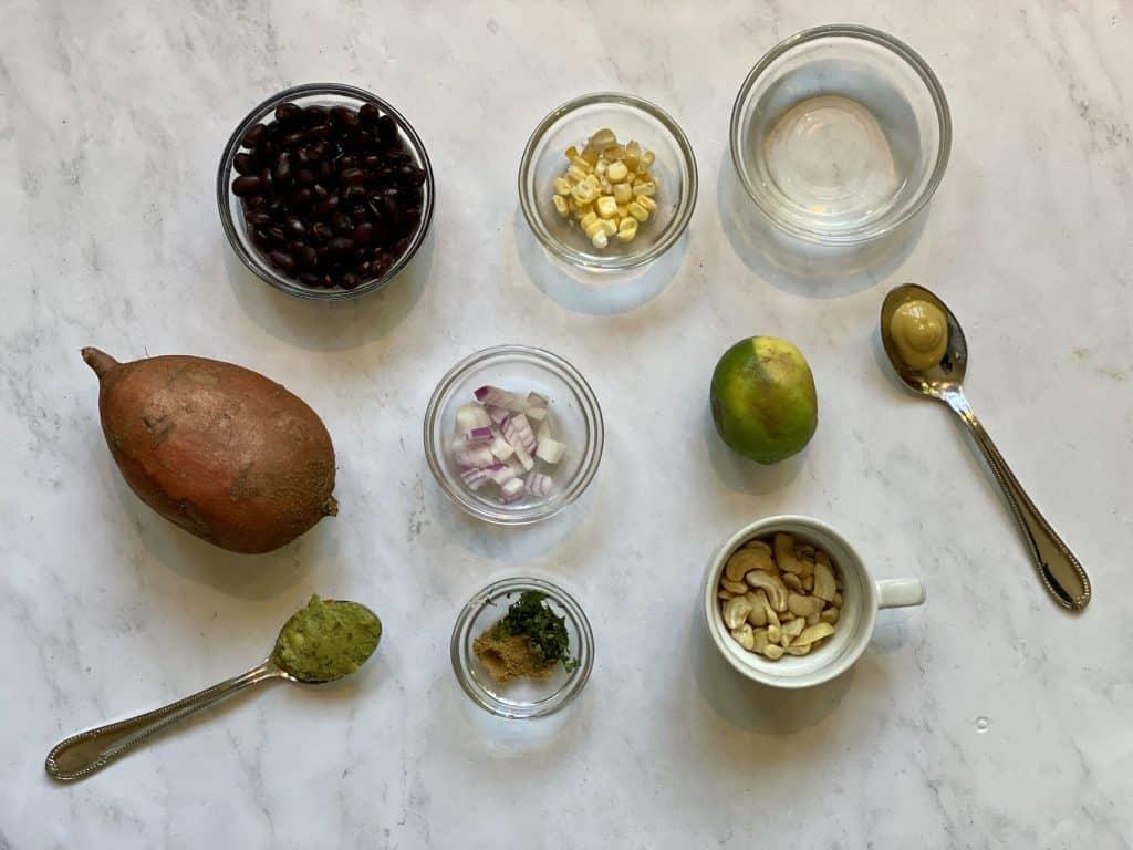 ingredients shown for vegan stuffed sweet potatoes, potatoes, black beans, corn, lime, cashews, cilantro, cumin, guacamole, vinegar, onions and mustard