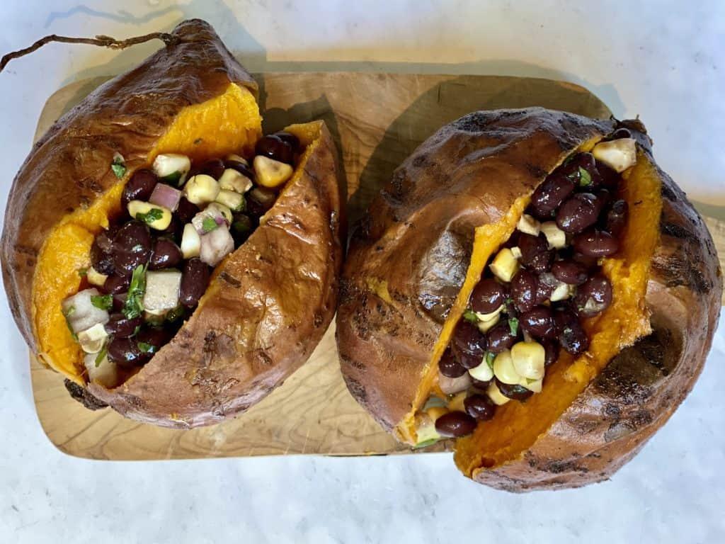 sweet potatoes cut open on a cutting board stuffed with black bean and corn salsa guacamole and cashew cream