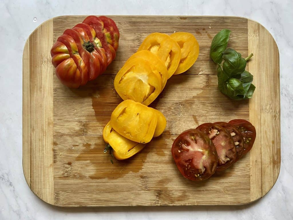 chopped tomatoes and basil for Caprese Salad Keto on a cutting board
