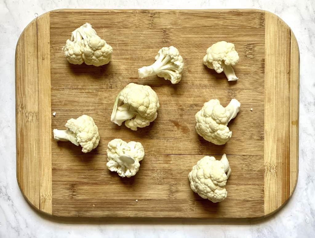 cauliflower florets on a cutting board for keto cauliflower wings