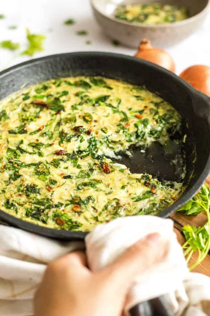 vegan eggless and crustless quiche in a nonstick skillet with greens