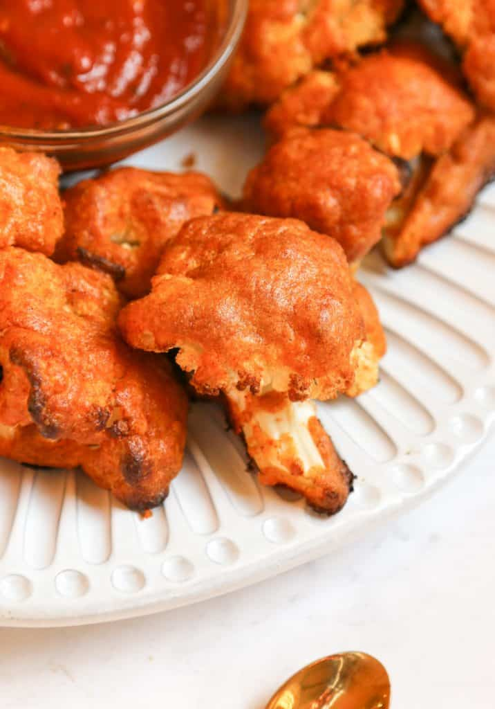 close up shot of keto cauliflower wings on a white plate with bbq dipping sauce