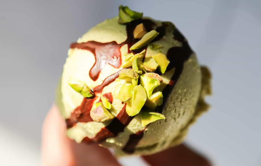 photo of vegan pistachio ice cream on a cone with chocolate drizzle and chopped pistachio nuts