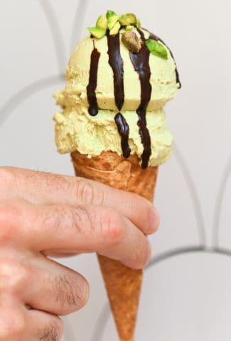 vegan pistachio ice cream on a sugar cone with chocolate syrup