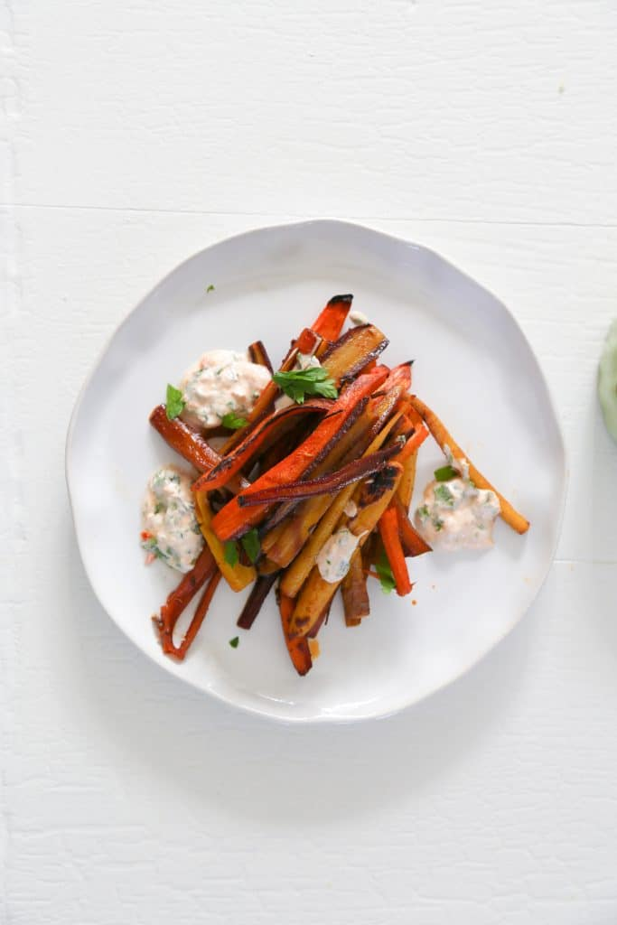 rainbow roasted carrots with yogurt dipping sauce on a plate.