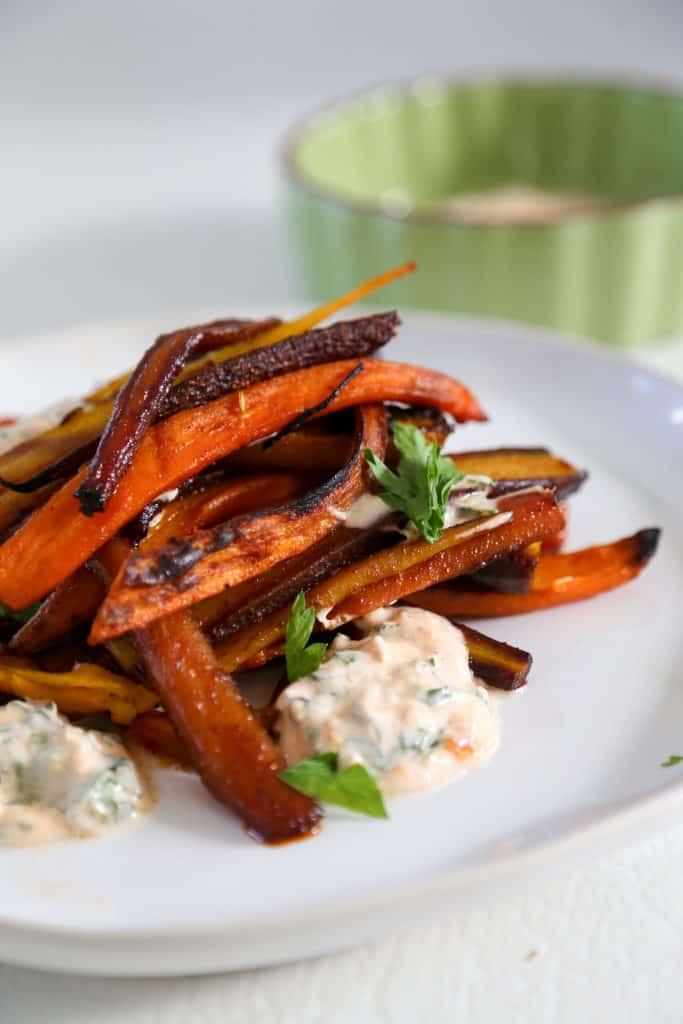 rainbow roasted carrots on a plate with harissa yogurt sauce.