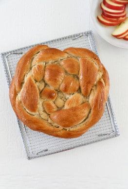 vegan round challah on a baking rack on a white table